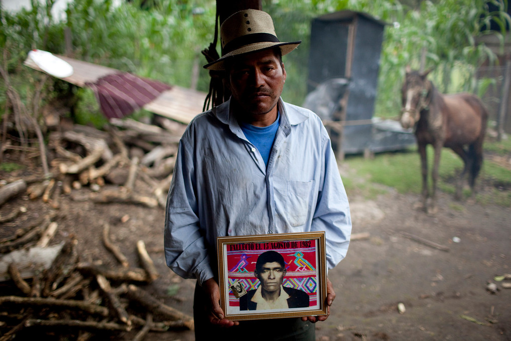 """. In this July 23, 2011, file photo, Tomas Raymundo Perez poses for a picture with a portrait of his father that reads \""""Died Aug. 13, 1982\"""" at his home in the municipality of Nebaj in Guatemala. Guatemalan soldiers allegedly killed Perez\'s family during a 1982 raid in the community of Vivitz. Twenty-nine years later, in June 2011, the Public Ministry brought charges against Gen. Hector Mario Lopez Fuentes in connection with the planning and ordering of bloody military operations that were part of the military plan coined \""""Victoria 82,\"""" among other crimes during his time as the Defense Ministry\'s Chief of Staff, including the extermination of residents in villages within the municipality of Nebaj during the government of Efrain Rios Montt (1982-1983). (AP Photo/Rodrigo Abd, file)"""
