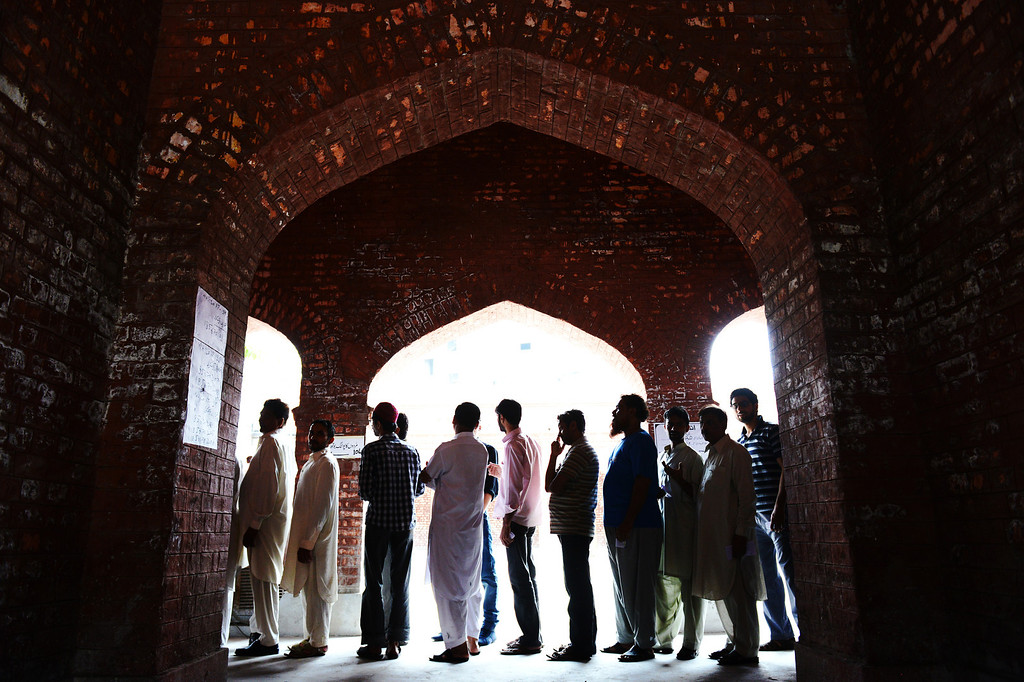 . Voters wait in line under arches at a polling station in Lahore during the general elections in Pakistan on May 11, 2013.  Pakistanis queued up to vote in landmark elections today, defying Taliban attacks to cast their ballots in polls marking a historic democratic transition for the nuclear-armed state.  More than 86 million people are eligible to vote for the 342-member national assembly and four provincial assemblies in Khyber Pakhtunkhwa, Punjab, Sindh and Baluchistan. ROBERTO SCHMIDT/AFP/Getty Images