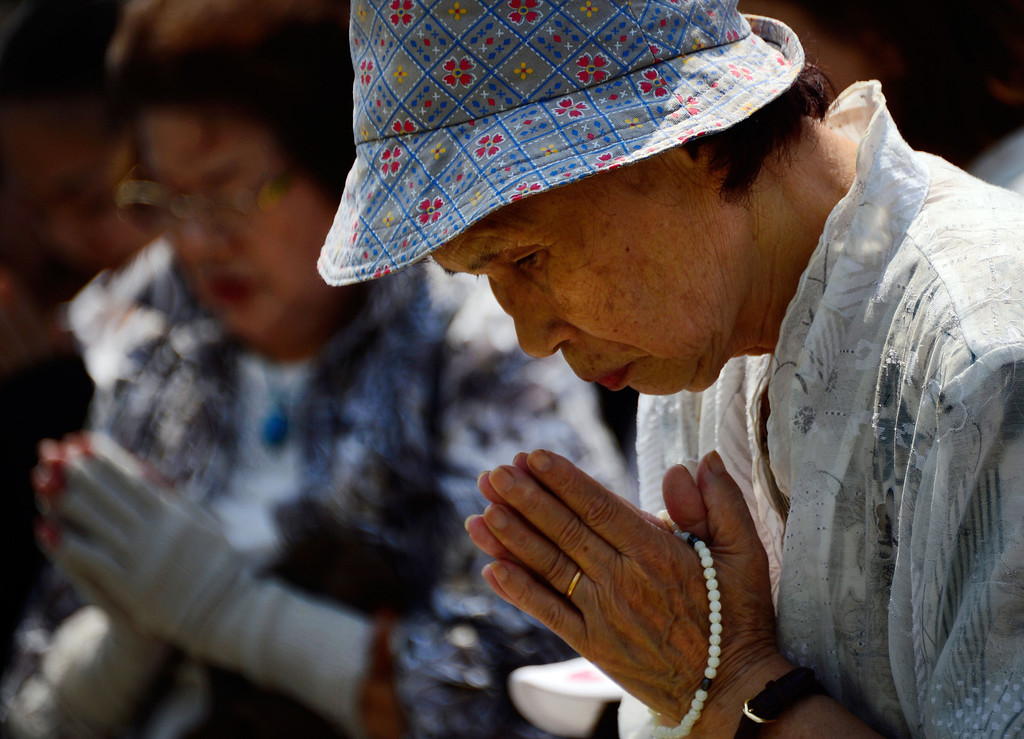 . Elderly women pray for victims of the 1945 atomic bombing in front of the cenotaph at the Peace Memorial Park in Hiroshima  on August 6, 2013 as ceremonies are held to mark the 68th anniversary of the bombing. Tens of thousands, including aging survivors, relatives, government officials and foreign delegates observed a moment of silence at 8:15 am local time, the time of the detonation which turned the city into a nuclear inferno in 1945.   AFP PHOTO / TORU  YAMANAKA/AFP/Getty Images