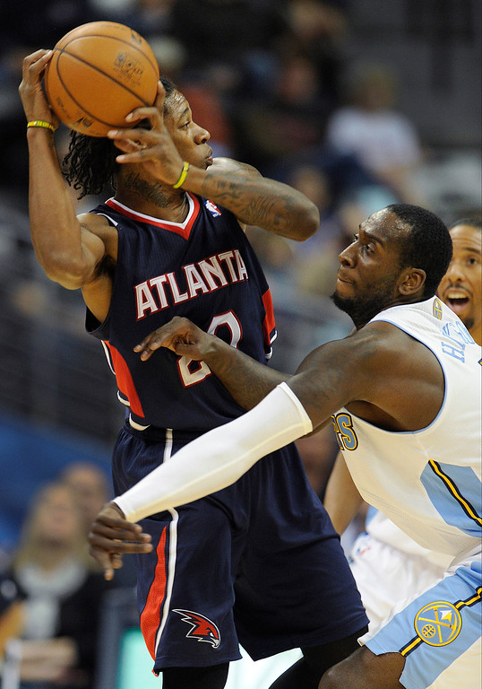 . Denver forward J.J. Hickson took a swipe at a ball held by Atlanta forward Cartier Martin in the first half.  Photo By Karl Gehring/The Denver Post