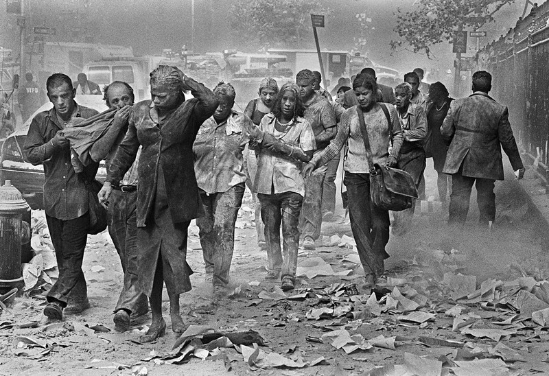 . Survivors of the World Trade Center terrorist attacks make their way through smoke, dust and debris on Fulton St., about a block from the collapsed towers, Tuesday, Sept. 11, 2001 in New York. (AP Photo/Gulnara Samoilova)