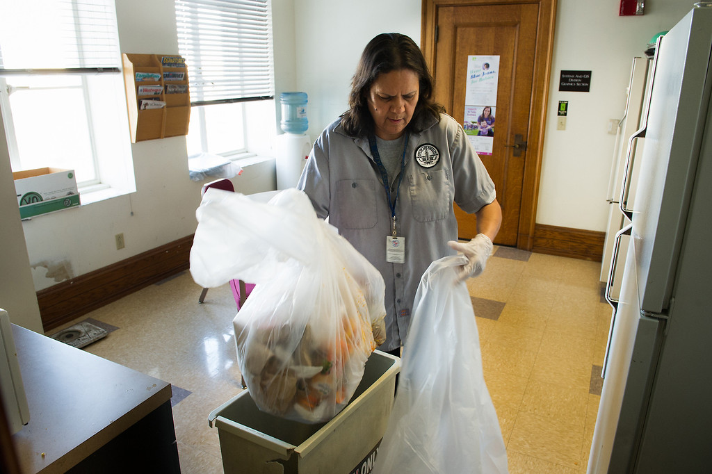 . Custodian Sanjuana Salas changes a trash bag in an office break room at L.A. City Hall, Tuesday, March 18, 2014. (Photo by Michael Owen Baker/L.A. Daily News)