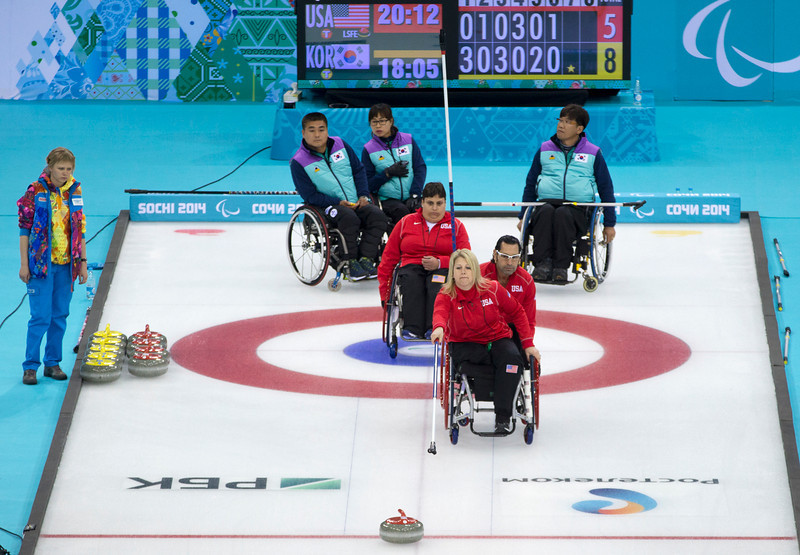 . United States\' Joseph Jimmy, steadies the chair of Penny Greely, as she throws and United States\' Meghan Lino, center, looks on and Korea\'s from left on top: Jong-Pan Kim, Mi-Suk Kang and Soon-Seok Seo look on during wheelchair curling match against Korea at the 2014 Winter Paralympics in Sochi, Russia, Saturday, March 8, 2014. Korea won 9-5. (AP Photo/Pavel Golovkin)