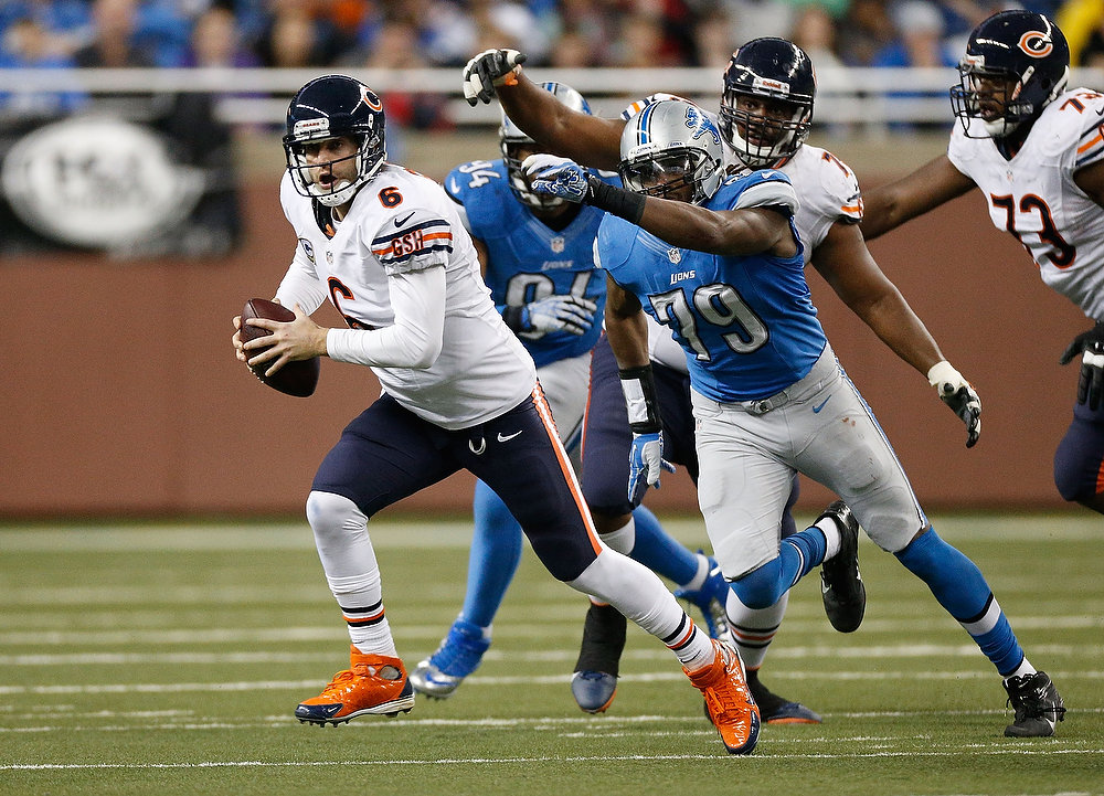 . Jay Cutler #6 of the Chicago Bears escapes the rush of Willie Young #79 of the Detroit Lions at Ford Field on December 30, 2012 in Detroit, Michigan. Chicago won the game 26-24. (Photo by Gregory Shamus/Getty Images)