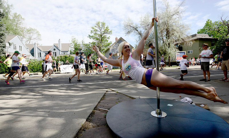 . Chrissy Fairbanks entertains runners while pole dances next to the course during the Bolder Boulder in Boulder, Colorado May 27, 2014.  DAILY CAMERA/ Mark Leffingwell