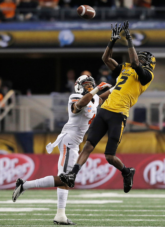 . Missouri wide receiver L\'Damian Washington (2) makes a reception over Oklahoma State cornerback Justin Gilbert (4) during the second half of the Cotton Bowl NCAA college football game, Friday, Jan. 3, 2014, in Arlington, Texas.  (AP Photo/Brandon Wade)