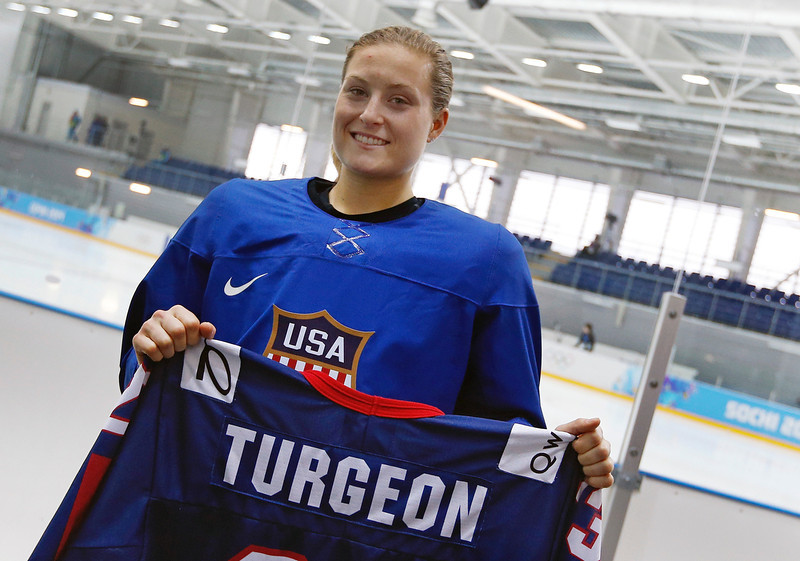 . Lyndsey Fry holds up the hockey jersey Tuesday, Feb. 11, 2014 in Sochi, Russia that belonged to her friend Liz Turgeon that she hand carried in her luggage to the 2014 Winter Olympics. Despondent over the death of Turgeon in a car accident, Fry nearly played herself out of contention for a spot on the U.S. women�s hockey team that was soon to be selected for the Sochi Olympics. Two years later she found motivation in her sorrow, telling her parents, �I�m going for it,� and rededicating herself to the sport that she and Turgeon shared. (AP Photo/Petr David Josek)