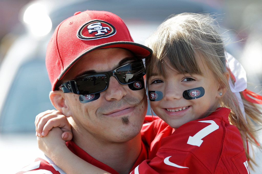 . San Francisco 49ers fan Chris Potter, left, holds his seven-year-old daughter Cailee while tailgating before an NFL preseason football game against the Denver Broncos, Thursday, Aug. 8, 2013, in San Francisco. (AP Photo/Marcio Jose Sanchez)