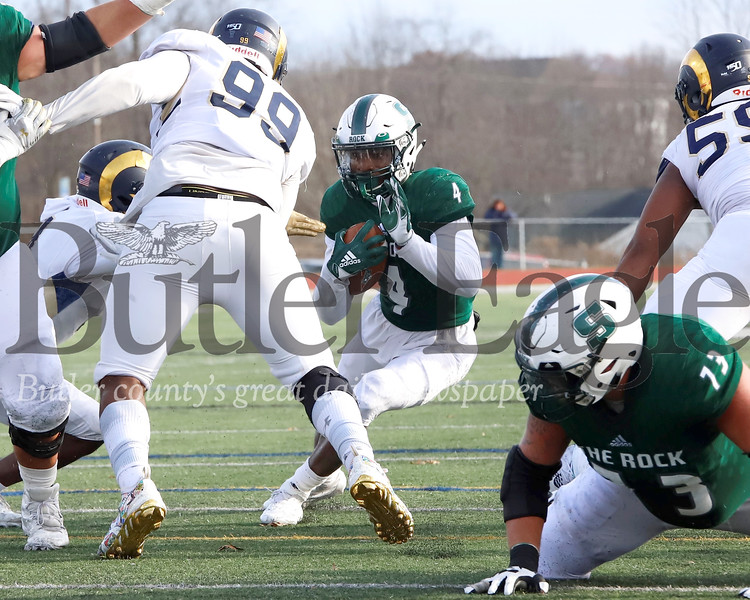 Slippery Rock running back Charles Snorweah (4) cuts inside against Shepherd University nose tackle Michael Holt (99) in Saturday's 51-30 home playoff win. Seb Foltz/Butler Eagle