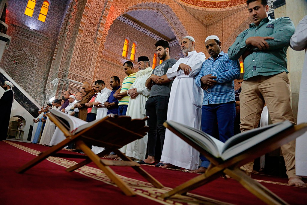 . Muslims attend prayers on the first day of Eid al-Fitr at the 17th Ramadan mosque in Baghdad, Iraq, Friday, June 15, 2018. Eid al-Fitr marks the end of the Muslims\' holy fasting month of Ramadan. (AP Photo/Karim Kadim)