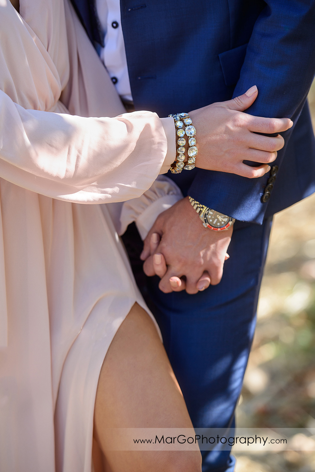 close-up of woman in pink dress and man in blue suit hands during Napa Valley engagement session at Castello di Amorosa in Calistoga