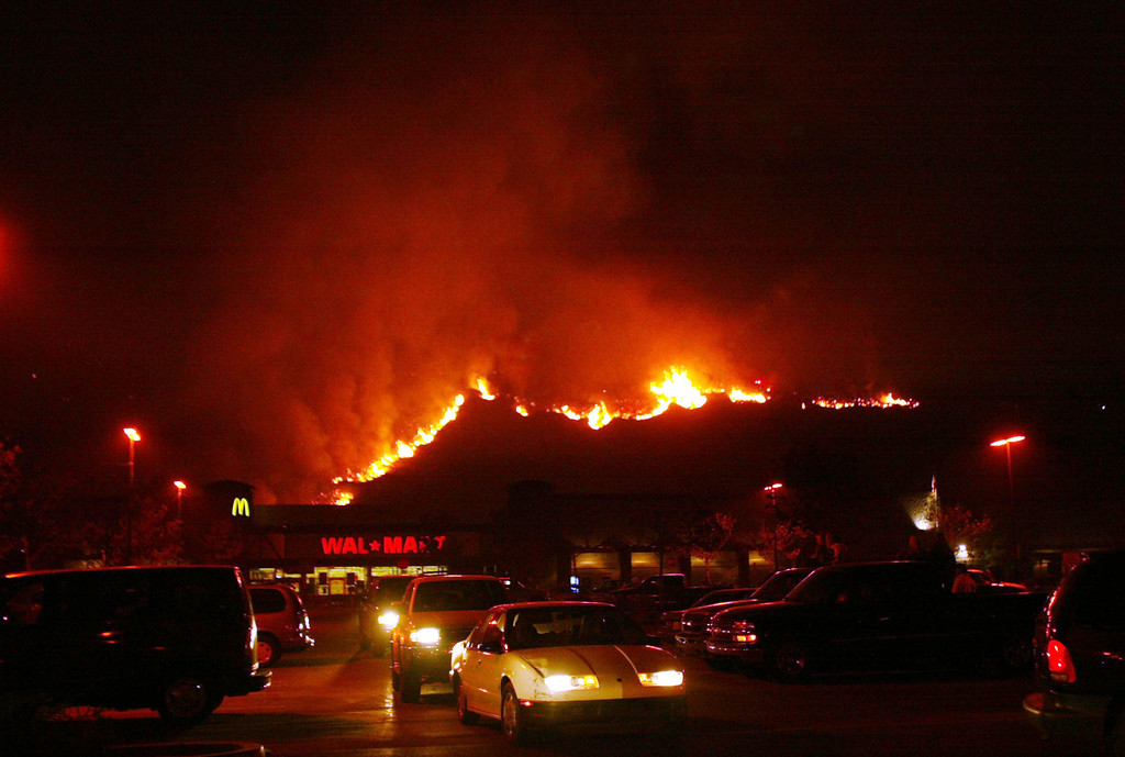 . SAN DIEGO - OCTOBER 27:  A fireline in the Cedar Fire makes its way down the hill near a Walmart October 27, 2003 near Lakeside in San Diego, California. The death toll stands at 13, with more than 1,000 homes being reduced to ashes as southern California fires continue to burn. Winds have eased a bit, but 30,000 homes remain threatened by the fires, which have charred more than 400,000 acres, according to officials. Davis, who has activated the National Guard, predicted damages will be in the billions of dollars.  (Photo by Donald Miralle/Getty Images)