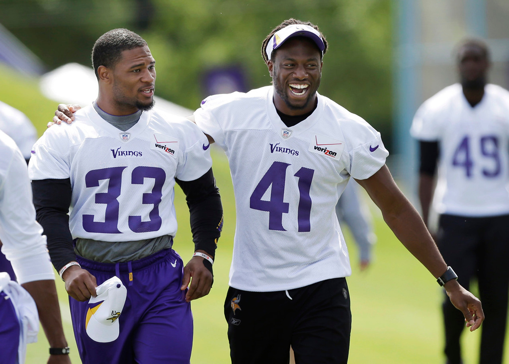 . Vikings safety Jamarca Sanford, left, walks off the field with ebullient safety Mistral Raymond after practice. (AP Photo/Charlie Neibergall)