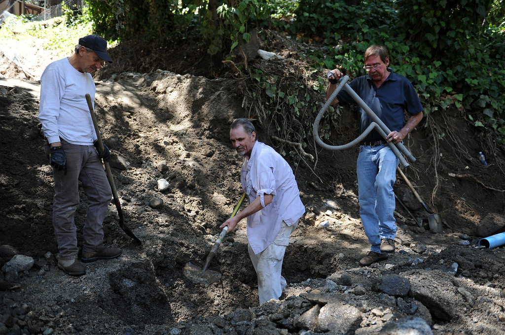 . Local landowners and shareholders of the Forest Park Mutual Water Company repair a water line after Sunday\'s storm caused flooding on Monday, August 4, 2014 in Forest Falls, Ca. (Micah Escamilla/San Bernardino Sun)