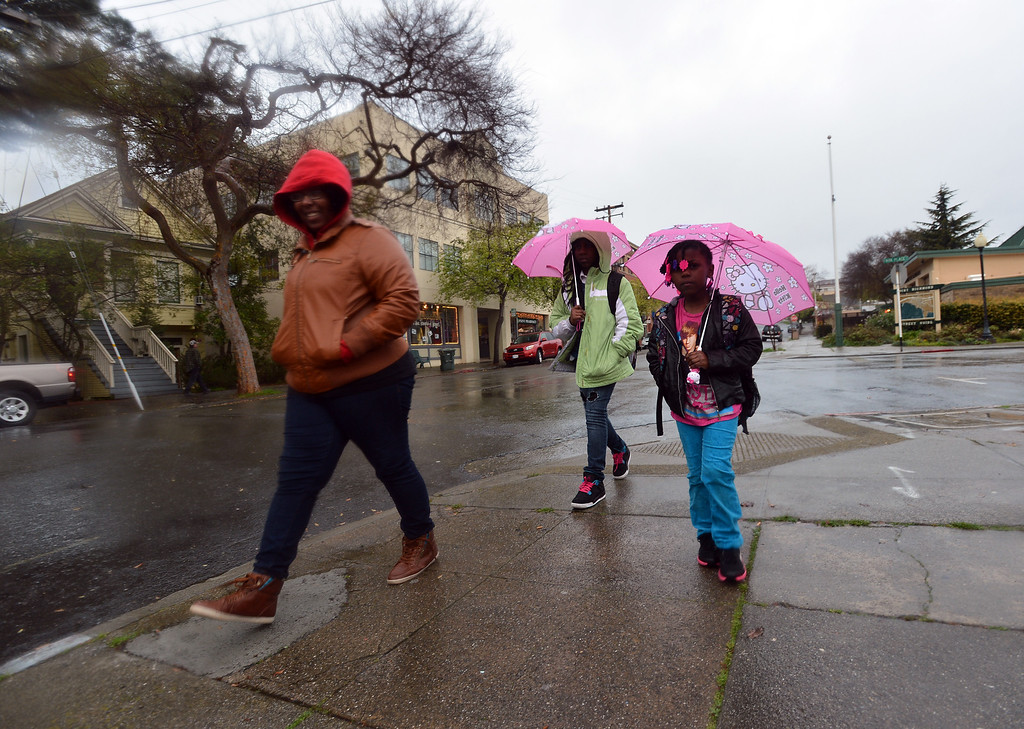 . On a drizzly morning, Erica Anderson walks her daughters, Akiyah, 5, right, and Samari, to school in the Point Richmond area of Richmond, Calif. on Thursday, Feb. 7, 2013. (Kristopher Skinner/Staff)