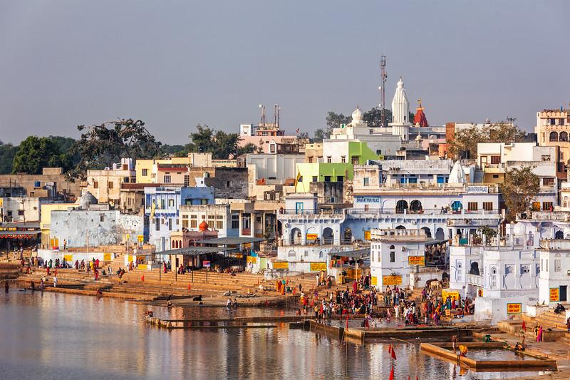 Hindu devotees bathing in sacred Puskhar Sagar lake on on ghats of  Pushkar, Rajasthan, India