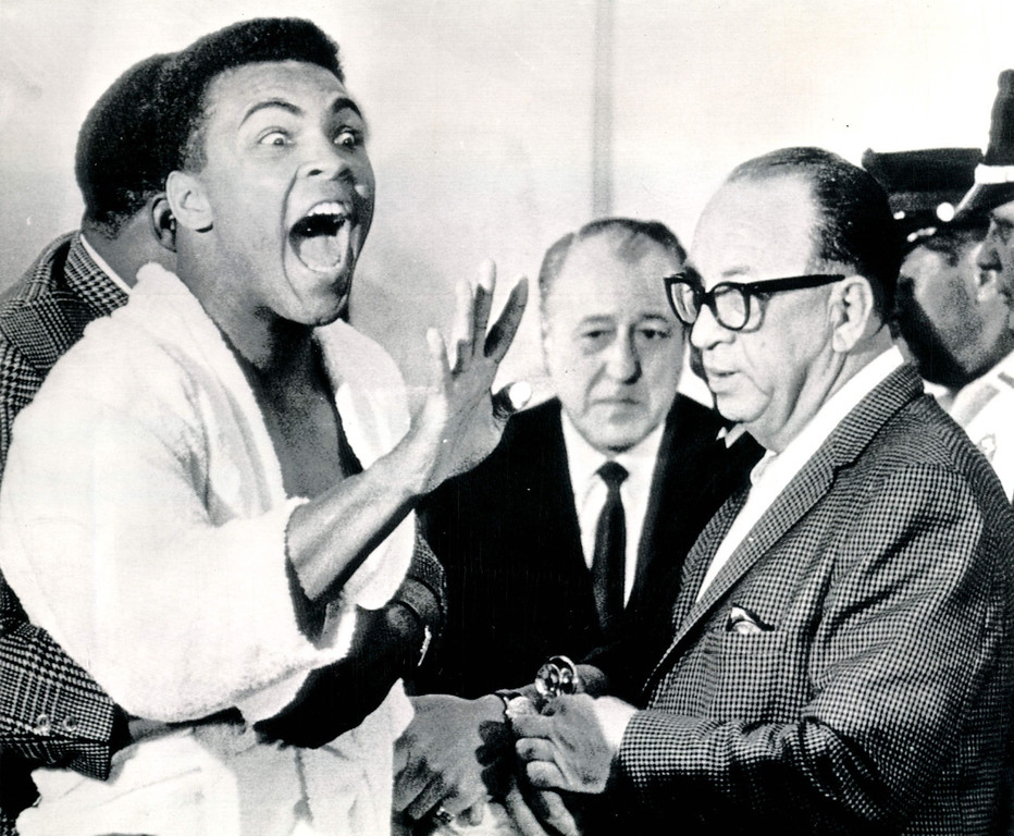 """. MIAMI BEACH, FLA, Feb. 25, 1964--DOCTOR SAYS CLAY SCARED TO DEATH--Challenger Cassius Clay makes a loud shout as Dr. Alexander Robbins, right, finishes his examination of Clay.  After examining Clay at the weigh-in-today Dr. Robbins said, \""""This is a man who is scared to death.  He is living in mortal fear.\""""  Clay meets heavyweight champion Sonny Liston in a title fight in Miami Beach.    Credit: AP"""