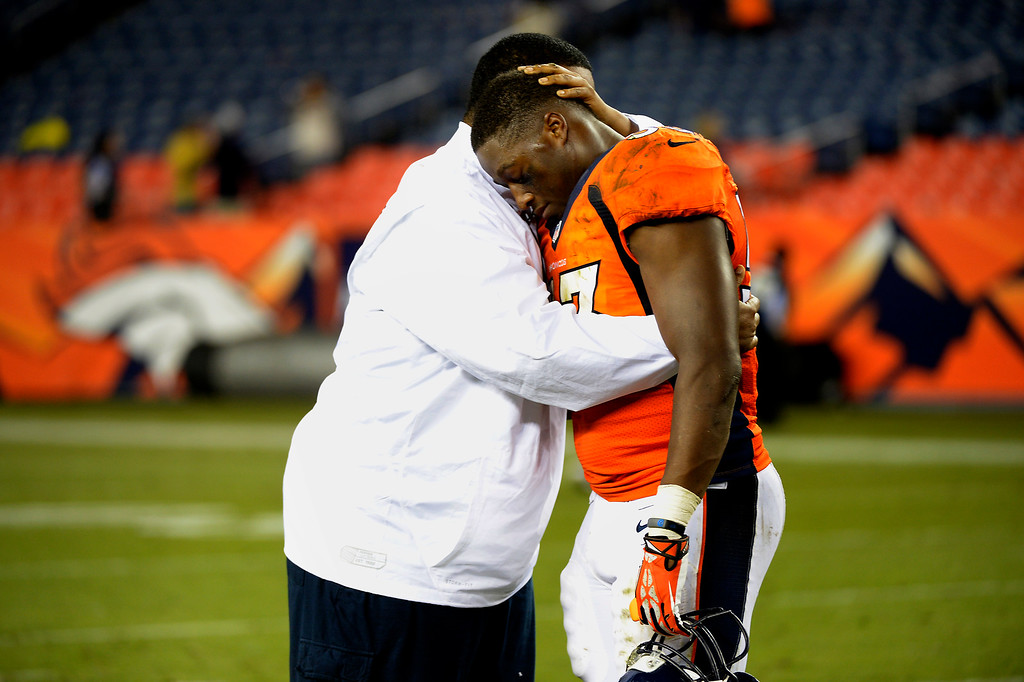 . DENVER, CO. - August 24: Linebacker Steven Johnson (53) of the Denver Broncos is hugged after the game by the team Chaplin Chip Simmons after the teams win vs the St. Louis Rams during the 3rd pre-season game of the season at Sports Authority Field at Mile High. August 24, 2013 Denver, Colorado. (Photo By Joe Amon/The Denver Post)