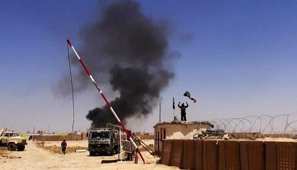 . This file image posted on a militant news Twitter account on Thursday, June 12, 2014 shows militants from the al-Qaida-inspired Islamic State of Iraq and the Levant (ISIL) people raising their flag at the entrance of an army base in Ninevah Province. Iraq. Days after Iraqís second-largest city fell to al-Qaida-inspired fighters, some Iraqis are already returning to Mosul, lured back by insurgents offering cheap gas and food, restoring power and water and removing traffic barricades. (AP Photo/albaraka_news, File)