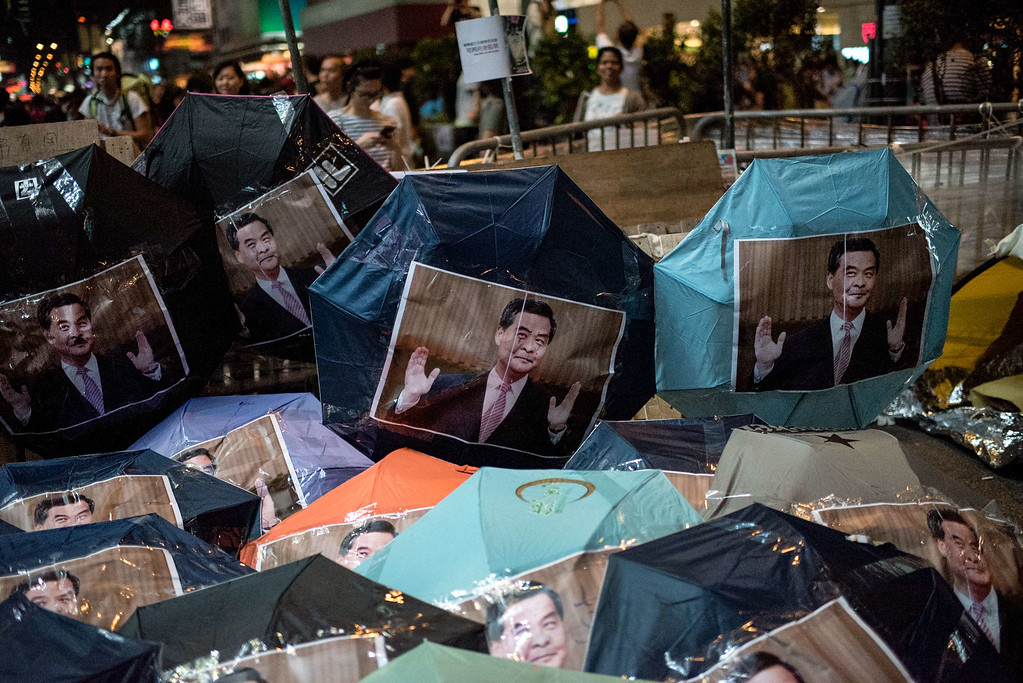 . Images of Hong Kong Chief Executive Leung Chun-ying are pasted onto umbrellas -- symbols of the Hong Kong pro-democracy protests -- at a barricade set up in the Mongkok district of Hong Kong on October 18, 2014. Pro-democracy demonstrators in Hong Kong clashed violently with police on October 18 as they reoccupied a protest camp mostly cleared the previous day, leading to multiple arrests and jeopardising government talks aimed at ending a political stalemate. AFP PHOTO / ALEX OGLEAlex Ogle/AFP/Getty Images