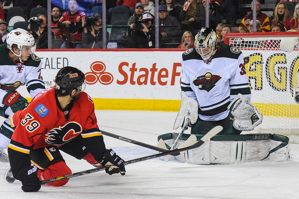 . T.J. Galiardi #39 of the Calgary Flames takes a backhand shot that gets past the defence of Darcy Kuemper #35 of the Minnesota Wild during an NHL game at Scotiabank Saddledome on February 1, 2014 in Calgary, Alberta, Canada. (Photo by Derek Leung/Getty Images)