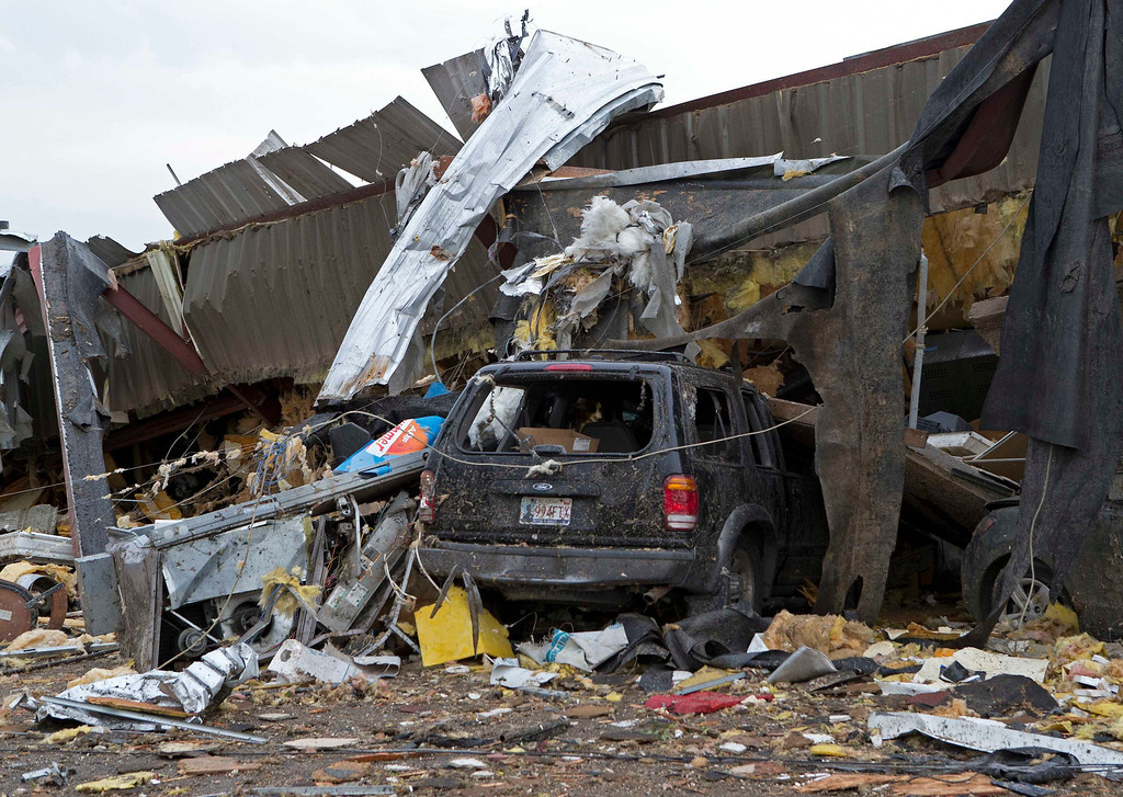 . A car is crushed by a fallen building after a huge tornado struck Moore, Oklahoma, near Oklahoma City, May 20, 2013. A massive tornado tore through the Oklahoma City suburb of Moore on Monday, killing at least 51 people as winds of up to 200 miles per hour (320 kph) flattened entire tracts of homes, two schools and a hospital, leaving a wake of tangled wreckage.    REUTERS/Richard Rowe