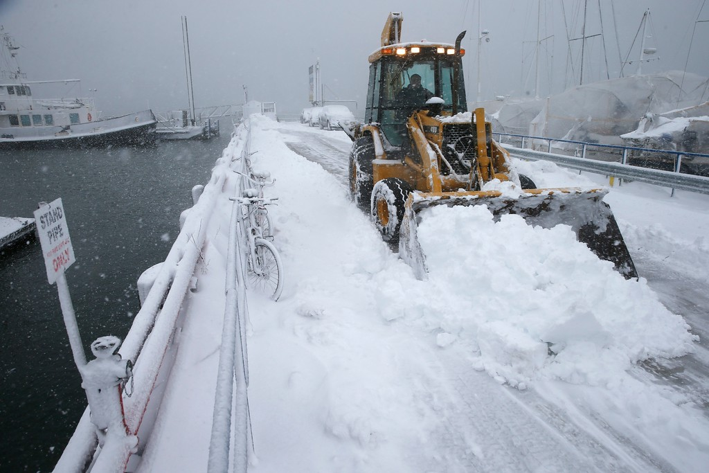 . A front end loader clears the pier at the Boston Harbor Shipyard and Marina in Boston, Tuesday, March 13, 2018. Boston finds itself in the bullseye of the third nor\'easter in two weeks, with forecasters warning of up to 18 inches of snow and 2 feet or more to the south. (AP Photo/Michael Dwyer)
