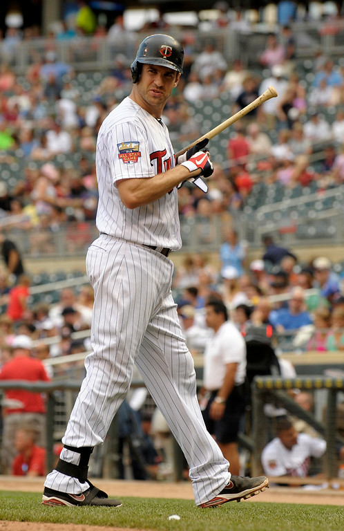 . Minnesota Twins\' Joe Mauer looks back at home plate umpire Eric Cooper afrter striking out with the bases loaded during the sixth inning of a baseball game against the Detroit Tigers in Minneapolis, Sunday, Aug. 24, 2014. Detroit won 13-4.(AP Photo/Tom Olmscheid)