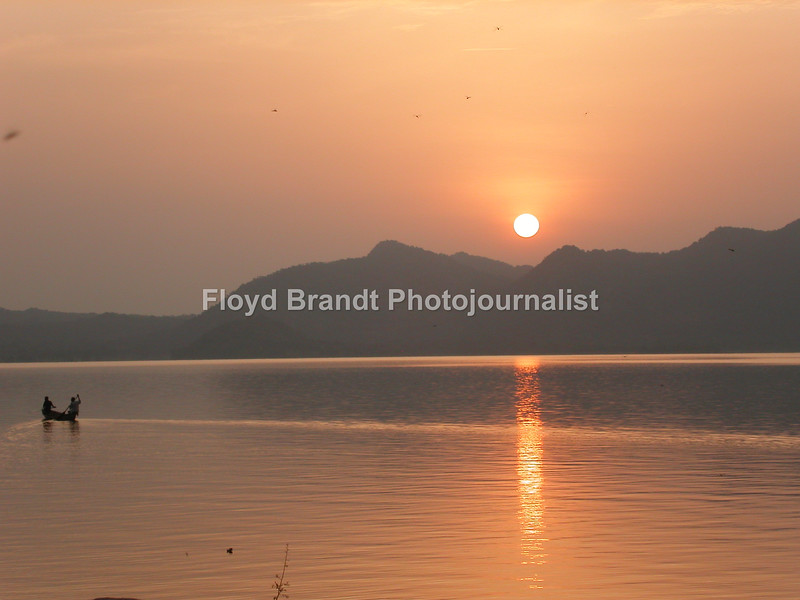 Floyd Brandt Photojournalist 40 days and nights in Cameroon Africa traveling from the South to the North. Sunset at Lagoon Blue where wild hippos live in the are and can be seen in the river.