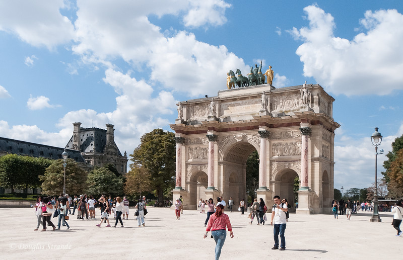 Small arch, the Arc de Triomphe du Carrousel located on the East end of Tuileries Garden features Napoleonic soldiers at the top of each pink pillar.