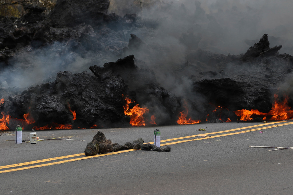 . In this Saturday, May 5, 2018, photo, lava burns across a road as an offering to the volcano goddess lies in the foreground in the Leilani Estates subdivision near Pahoa, Hawaii. Glowing plumes of lava have shot hundreds of feet into the air at points, officials said, and black-and-orange ribbons of rock have curled into roadways. (AP Photo/Caleb Jones)