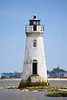 Old white lighthouse sitting off the coast in a bay.