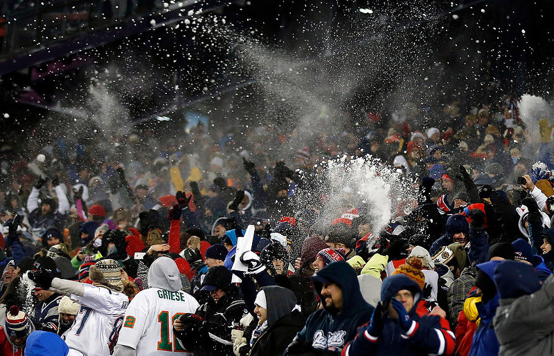 . New England Patriots fans toss snow to celebrate a touchdown run by running back Stevan Ridley during the second quarter of an NFL football game against the Miami Dolphins in Foxborough, Mass., Sunday, Dec. 30, 2012. (AP Photo/Charles Krupa)