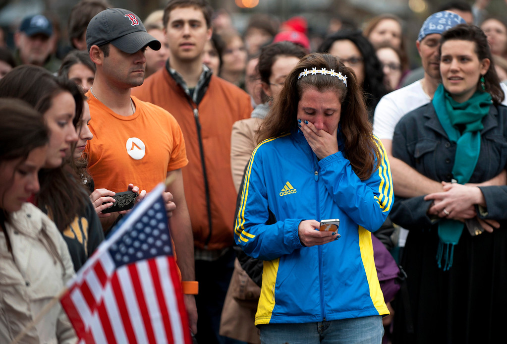 ". A woman, wearing a Boston Marathon 2013 jacket, cries as people gather in the Boston Commons for a vigil on April 16, 2013 in Boston, in the aftermath of two explosions that struck near the finish line of the Boston Marathon on April 15. Investigators said the range of suspects and motives in the grisly Boston bombings remained ""wide open\"" as experts assessed remnants of the crude devices designed to inflict maximum suffering.   DON EMMERT/AFP/Getty Images"
