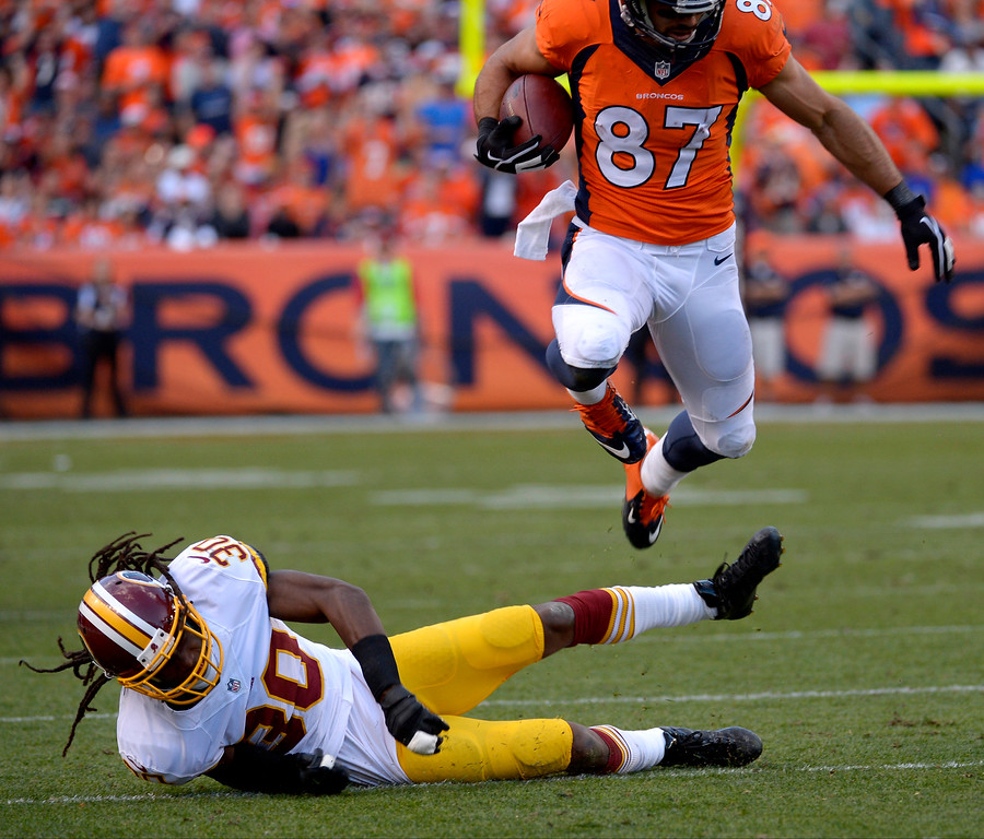 . Denver Broncos wide receiver Eric Decker (87) jumps over Washington Redskins cornerback E.J. Biggers (30) after catching a pass during the second half.   (Photo by Tim Rasmussen/The Denver Post)