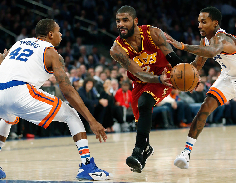 . New York Knicks guard Brandon Jennings (3) fouls Cleveland Cavaliers guard Kyrie Irving (2) as Irving drives into the pain with New York Knicks forward Lance Thomas (42) defending in the first quarter of an NBA basketball game at Madison Square Garden in New York, Wednesday, Dec. 7, 2016. (AP Photo/Kathy Willens)