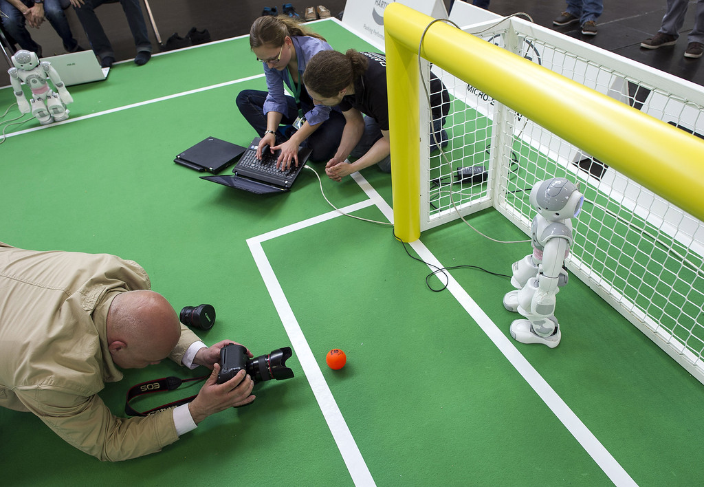 . MAGDEBURG, GERMANY - APRIL 26:  A Photographer takes a picture at the 2013 RoboCup German Open tournament on April 26, 2013 in Magdeburg, Germany. The robots, which are a model called Nao, manufactured by Aldebaran Robotics, perform autonomously and communicate with one another via WLAN. The three-day tournament is hosting 43 international teams and 158 German junior teams that compete in a variety of disciplines, including soccer, rescue and dance.  (Photo by Jens Schlueter/Getty Images)