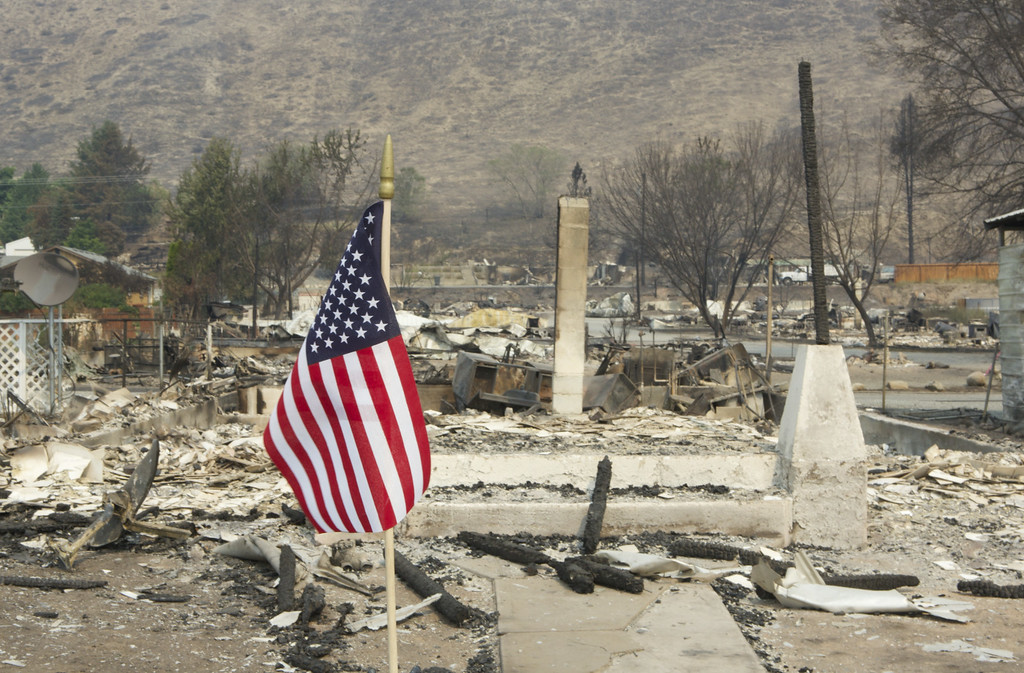 . A United States flag is displayed amid the ruins of a block of homes following a wildfire  July 20, 2014 in Pateros, Washington. Several fires throughout the state have destroyed hundreds of home forced evacuations and continue to threaten more communities. (Stephen Brashear/Getty Images)