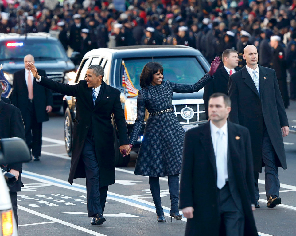 . U.S. President Barack Obama and first lady Michelle Obama walk down Constitution Avenue after emerging from the presidential limousine during the inaugural parade from the Capitol to the White House in Washington, January 21, 2013.   REUTERS/Jason Reed
