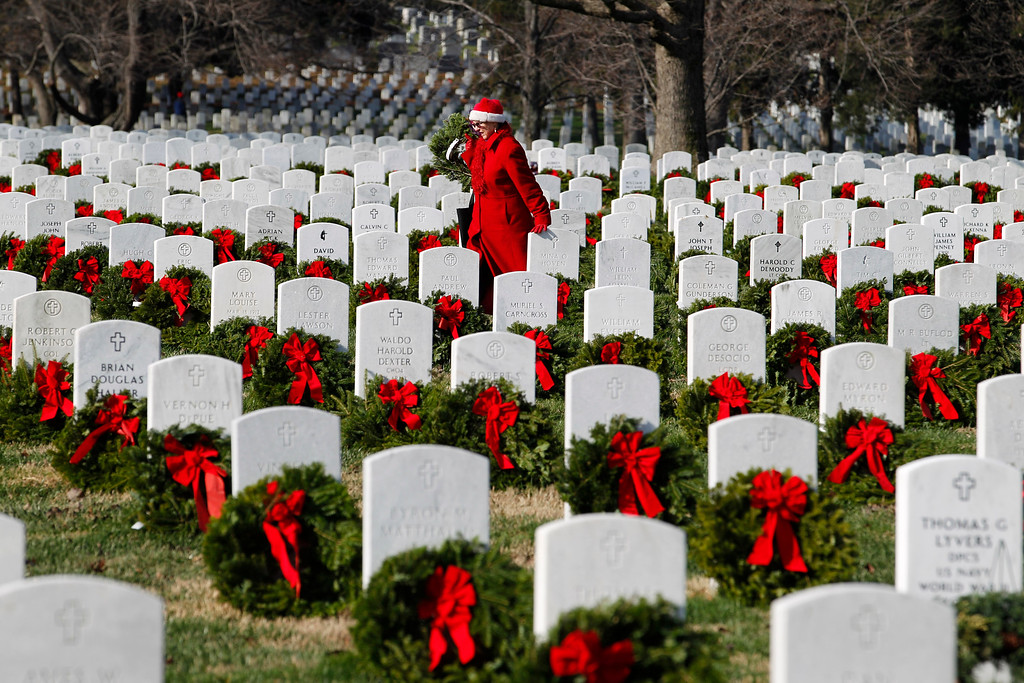 . Volunteer Pati Redmond of Frederick, Md., helps to lay holiday wreaths over the graves of fallen soldiers at Arlington National Cemetery in Washington Saturday Dec. 10, 2011, during Wreaths Across America Day. (AP Photo/Jose Luis Magana)