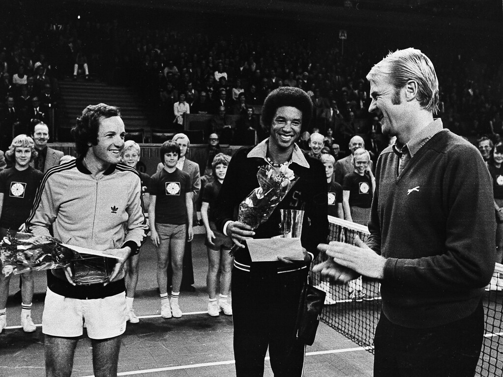 . Two happy tennis players, Tom Okker, left and Arthur Ashe, center, with Swedish tennis player Janne Lundquist, following the final Stockholm Open tennis tournament, Nov. 1974.   (AP Photo)