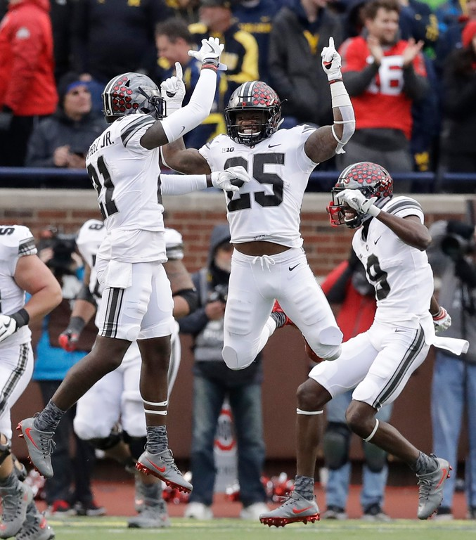 . Ohio State running back Mike Weber (25) jumps with wide receiver Parris Campbell (21) and wide receiver Binjimen Victor (9) after Weber\'s touchdown during the second half of an NCAA college football game against Michigan, Saturday, Nov. 25, 2017, in Ann Arbor, Mich. Ohio State won 31-20. (AP Photo/Carlos Osorio)