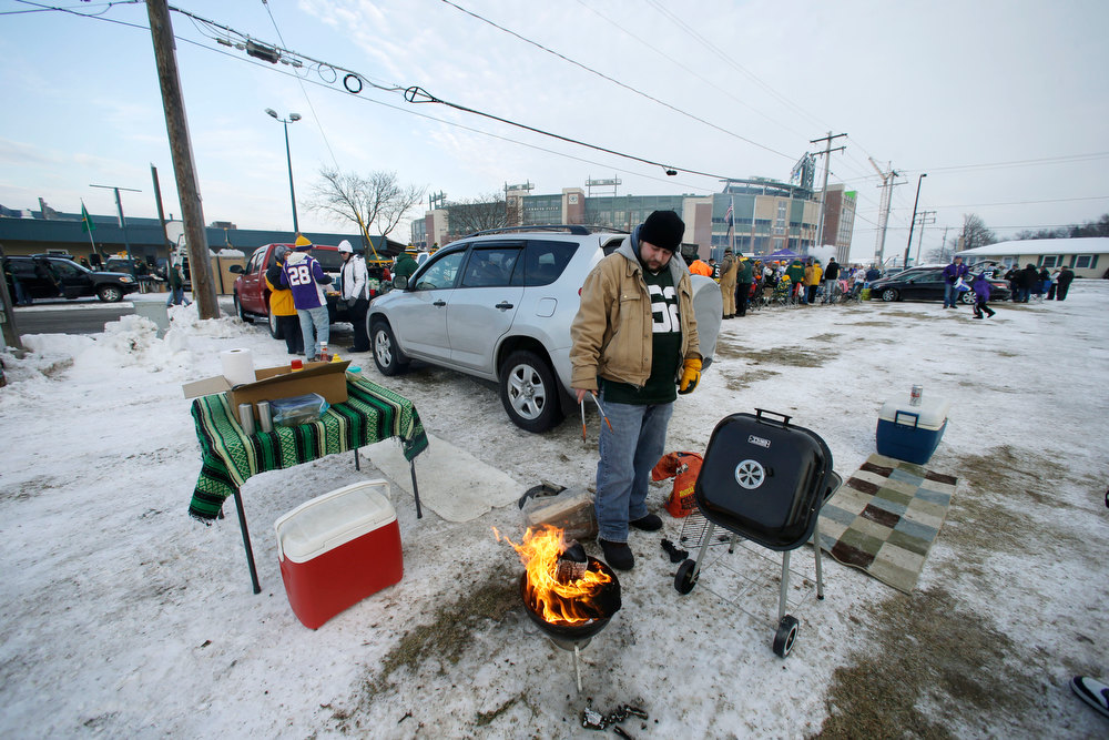 . A tailgater fires up a grill before an NFL wild card playoff football game between the Green Bay Packers and the Minnesota Vikings Saturday, Jan. 5, 2013, in Green Bay, Wis. (AP Photo/Jeffrey Phelps)