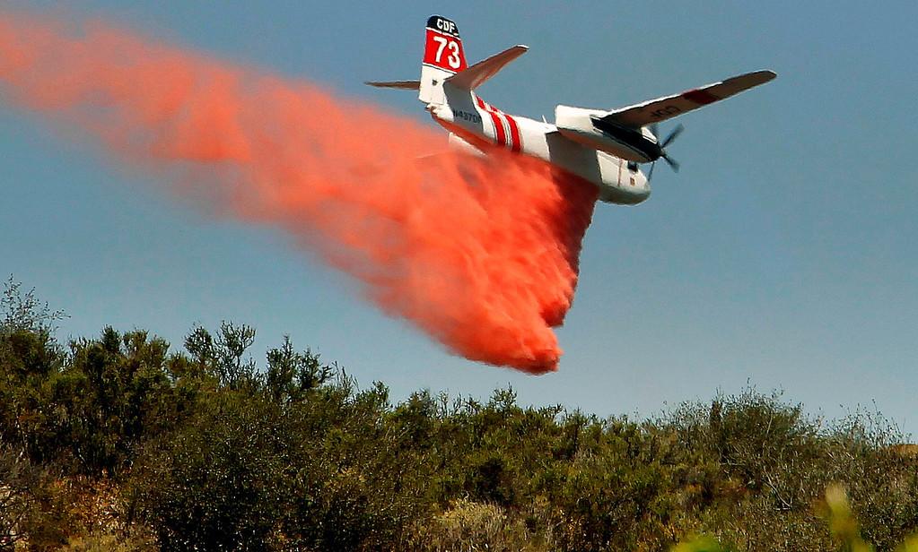 . A firefighting aircraft drops fire retardant along a hill side near Thousand Oaks, Calif. on Thursday, May 2, 2013. (AP Photo/Nick Ut)