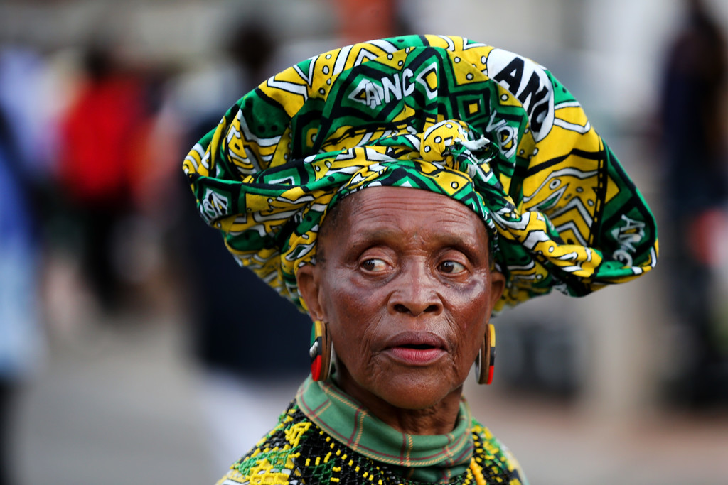 . A woman wears the colors of the ANC as people sing and dance to celebrate the life of Nelson Mandela outside his former home in Vilakazi Street, Soweto Township, on December 7, 2013 in Soweto, South Africa. Mandela became South Africa\'s first black president in 1994 after spending 27 years in jail for his activism against apartheid in a racially-divided South Africa. (Photo by Christopher Furlong/Getty Images)
