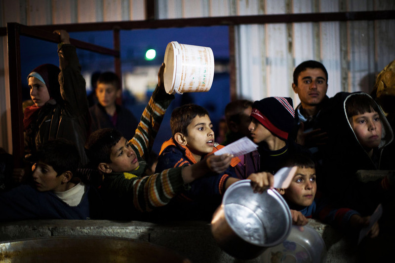 . Syrian children wait in line for food distribution at a refugee camp near the Turkish border, in Azaz, Syria, Sunday, Dec. 9, 2012. (AP Photo/Manu Brabo)