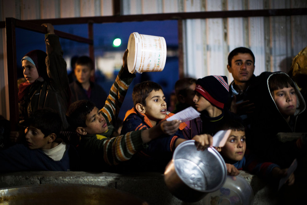 Description of . Syrian children wait in line for food distribution at a refugee camp near the Turkish border, in Azaz, Syria, Sunday, Dec. 9, 2012. (AP Photo/Manu Brabo)