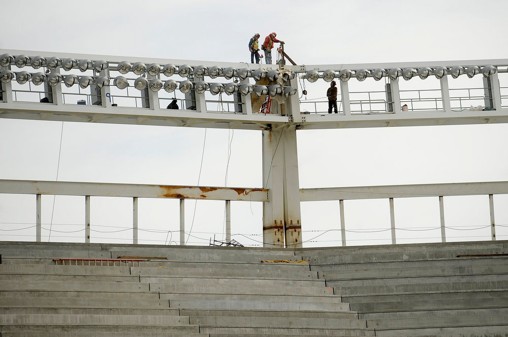 Description of . Workers check construction near a lighting array atop Santa Clara Stadium, the future home of the NFL's San Francisco 49'ers, in Santa Clara, California March 6, 2013. The stadium is scheduled to open in time for the 2014 NFL season.  REUTERS/Noah Berger