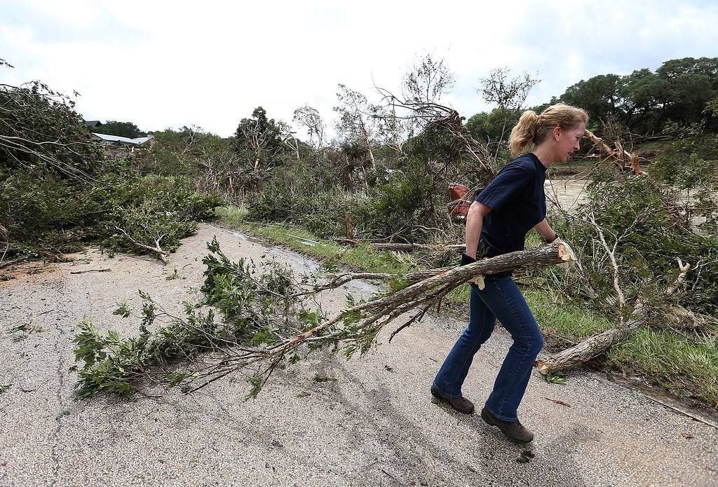 . Andrea Jones helps remove a downed tree on River Road, Monday, May 25, 2015, in Wimberley, Texas. Around a dozen people were reported missing in flash flooding from a line of storms that stretched from the Gulf of Mexico to the Great Lakes. (Jerry Lara/The San Antonio Express-News via AP)