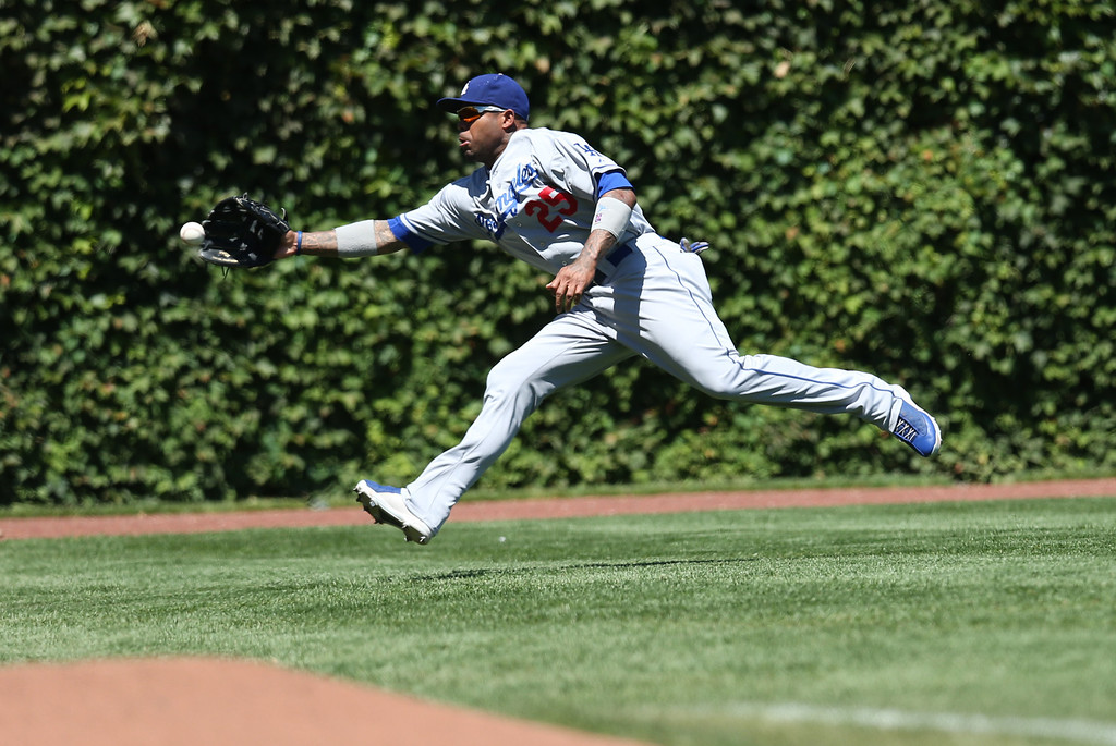 . CHICAGO, IL - AUGUST 04: Carl Crawford #25 of the Los Angeles Dodgers can\'t make a catch on a double off the bat of Dioner Navarro #30 of the Chicago Cubs during the first inning  on August 4, 2013 at Wrigley Field in Chicago, Illinois.  (Photo by Jonathan Daniel/Getty Images)
